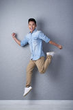 Studio Shot of Asian Man in Motion. Full length portrait of joyful young man looking at camera with toothy smile while jumping in air, studio shot Royalty Free Stock Photos