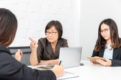 Studio shot of Asian, senior businesswoman with laptop, sitting with two young staffs in board room in office, boss making serious. Comment and point to one of stock image
