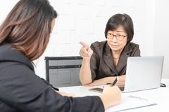 Studio shot of Asian, senior businesswoman with laptop, sitting with two young staffs in board room in office, boss making serious stock photo