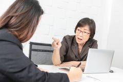 Studio shot of Asian, senior businesswoman with laptop, sitting with two young staffs in board room in office, boss making serious royalty free stock photo