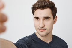 Studio shot of attractive cute man with stylish haircut and pleases expression taking selfie on smartphone, standing. Over gray background. Social media fan stock images
