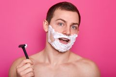 Studio shot of attractive guy posing with razor in bathroom, standing with cream on face and opened mouth, has surprised facial. Expression,  over pink stock photography