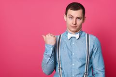 Studio shot of attractive male in blue shirt, suspenders and white bow tie, shows with thumb finger aside, isolated over pink. Studio background. Copy space for stock photos