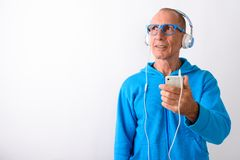 Studio shot of bald senior man holding mobile phone while thinki. Ng and listening to music with eyeglasses against white background stock photos