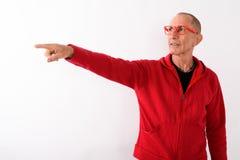 Studio shot of bald senior man pointing at distance while wearin. G eyeglasses against white background stock photo