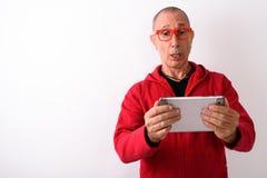 Studio shot of bald senior man using digital tablet while lookin. G shocked and wearing eyeglasses against white background stock photo