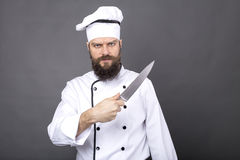 Studio shot of a bearded chef holding a big sharp knife. Over gray background Royalty Free Stock Photos