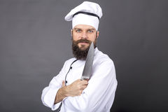 Studio shot of a bearded chef holding a big sharp knife. Over gray background Royalty Free Stock Photography