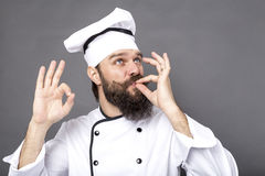 Studio shot of a bearded chef showing OK sign Stock Photos