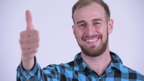 Face of happy bearded hipster man giving thumbs up. Studio shot of bearded hipster man against white background stock video footage