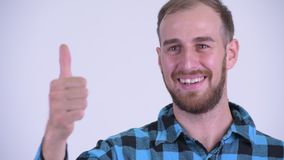 Face of happy bearded hipster man giving thumbs up. Studio shot of bearded hipster man against white background stock footage