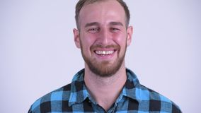Face of happy bearded hipster man laughing. Studio shot of bearded hipster man against white background stock video