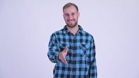 Happy bearded hipster man giving handshake. Studio shot of bearded hipster man against white background stock video footage