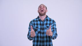 Happy bearded hipster man giving thumbs up and looking excited. Studio shot of bearded hipster man against white background stock footage