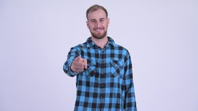 Happy bearded hipster man pointing at camera and giving thumbs up. Studio shot of bearded hipster man against white background stock video