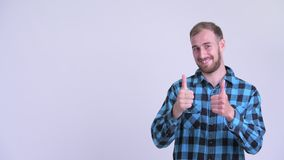 Happy bearded hipster man pointing up and giving thumbs up. Studio shot of bearded hipster man against white background stock footage