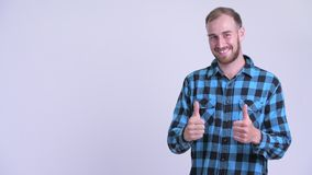 Happy bearded hipster man snapping fingers and giving thumbs up. Studio shot of bearded hipster man against white background stock footage