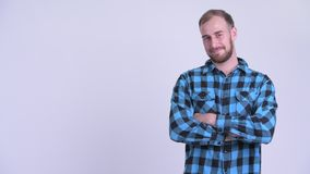 Happy bearded hipster man touching something and crossing arms. Studio shot of bearded hipster man against white background stock video footage