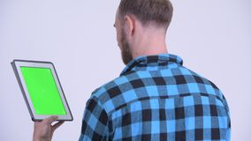 Rear view of bearded hipster man using digital tablet. Studio shot of bearded hipster man against white background stock video footage