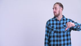Sad bearded hipster man showing something and giving thumbs down. Studio shot of bearded hipster man against white background stock video footage