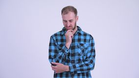 Serious bearded hipster man thinking and looking down. Studio shot of bearded hipster man against white background stock video