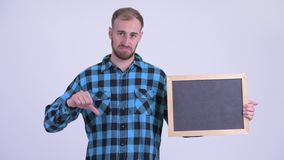 Stressed bearded hipster man holding blackboard and giving thumbs down. Studio shot of bearded hipster man against white background stock footage