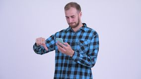 Stressed bearded hipster man using phone and getting bad news. Studio shot of bearded hipster man against white background stock video footage
