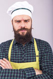 Studio shot of a bearded man with apron holding arms folded Royalty Free Stock Image