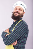 Studio shot of a bearded man with cook hat  holding arms crossed Royalty Free Stock Photos