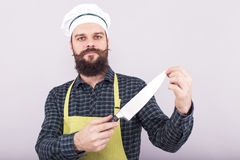 Studio shot of a bearded man holding a big sharp knife. Over gray background Royalty Free Stock Images