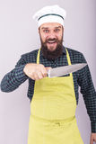 Studio shot of a bearded man holding a big sharp knife. Over gray background Stock Photos