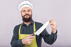 Studio shot of a bearded man holding a big sharp knife. Over gray background Stock Photography