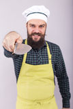 Studio shot of a bearded man holding a big sharp knife. Over gray background Stock Images