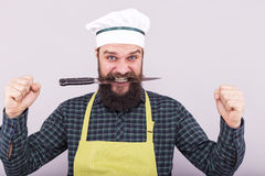 Studio shot of a bearded man holding a sharp knife with his teet. H over gray background Royalty Free Stock Images