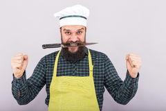 Studio shot of a bearded man holding a sharp knife with his teet. H over gray background Stock Photography