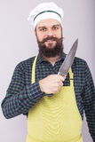 Studio shot of a bearded man holding a sharp knife. Over gray background Stock Photography