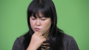 Head shot of serious overweight Asian woman thinking. Studio shot of beautiful overweight Asian woman against chroma key with green background stock video