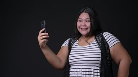 Beautiful overweight Asian woman using mobile phone against black background. Studio shot of beautiful overweight Asian woman using mobile phone against black stock video footage