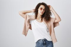 Studio shot of beautiful urban woman with curly hair raising hands sensually, wearing trendy sunglasses and sweater over. Shoulders, posing against gray Royalty Free Stock Image