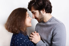 Studio shot of beautiful young couple looking at each other with love holding their hands together.,Handsome guy and pretty girl s. Tanding together over white Stock Images