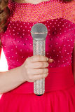 Studio shot beautiful young singing girl in elegant red dress lo. Oking at the camera with rhinestone microphone. image on a white studio background Stock Photo