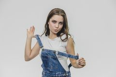 Studio shot a beautiful young woman in denim overalls. Working clothes staging and looking at the camera. royalty free stock photography