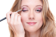 Studio shot of beautiful young woman doing make up stock images