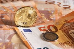 Studio shot of bitcoin physical golden coin on 50 euro bills banknotes. Bitcoin is a blockchain crypto currency. Studio shot of bitcoin physical golden coin on Royalty Free Stock Photography