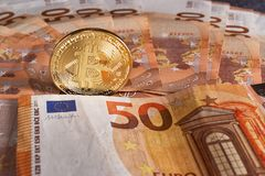 Studio shot of bitcoin physical golden coin on 50 euro bills banknotes. Bitcoin is a blockchain crypto currency. Studio shot of bitcoin physical golden coin on Royalty Free Stock Images