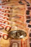 Studio shot of bitcoin physical golden coin on 50 euro bills banknotes. Bitcoin is a blockchain crypto currency. Studio shot of bitcoin physical golden coin on Stock Image