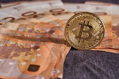 Studio shot of bitcoin physical golden coin on 50 euro bills banknotes. Bitcoin is a blockchain crypto currency. Studio shot of bitcoin physical golden coin on Stock Images