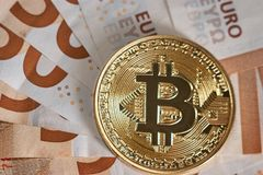 Studio shot of bitcoin physical golden coin on 50 euro bills banknotes. Bitcoin is a blockchain crypto currency. Macro. Studio shot of bitcoin physical golden Stock Photography