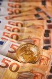 Studio shot of bitcoin physical golden coin on 50 euro bills banknotes. Bitcoin is a blockchain crypto currency. Studio shot of bitcoin physical golden coin on Stock Photos