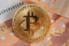 Studio shot of bitcoin physical golden coin on 50 euro bills banknotes. Bitcoin is a blockchain crypto currency. Macro. Studio shot of bitcoin physical golden Royalty Free Stock Photography
